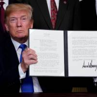 U.S. President Donald Trump holds his signed memorandum on intellectual property tariffs on high-tech goods from China, at the White House in Washington in March. | REUTERS
