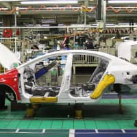 A worker assembles a vehicle at the Toyota Motor Corp. factory in Burnaston, U.K., in February 2011. | BLOOMBERG