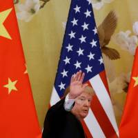 U.S. President Donald Trump waves while making joint statements with China's President Xi Jinping at the Great Hall of the People in Beijing in November 2017. | REUTERS