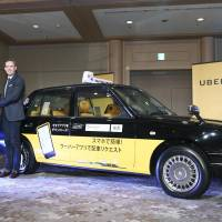 Uber Technologies Inc.'s Japan head Tom White (right) and Fuji Taxi Group President Hisashi Umemura pose as Uber announced a plan to launch a ride-hailing app for taxis operating in Nagoya on Thursday. | KYODO