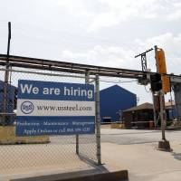 A help wanted sign hangs outside the U.S. Steel Granite City Works facility in Granite City, Illinois, in June. On Tuesday, the Labor Department reports on job openings and labor turnover for July. | AP