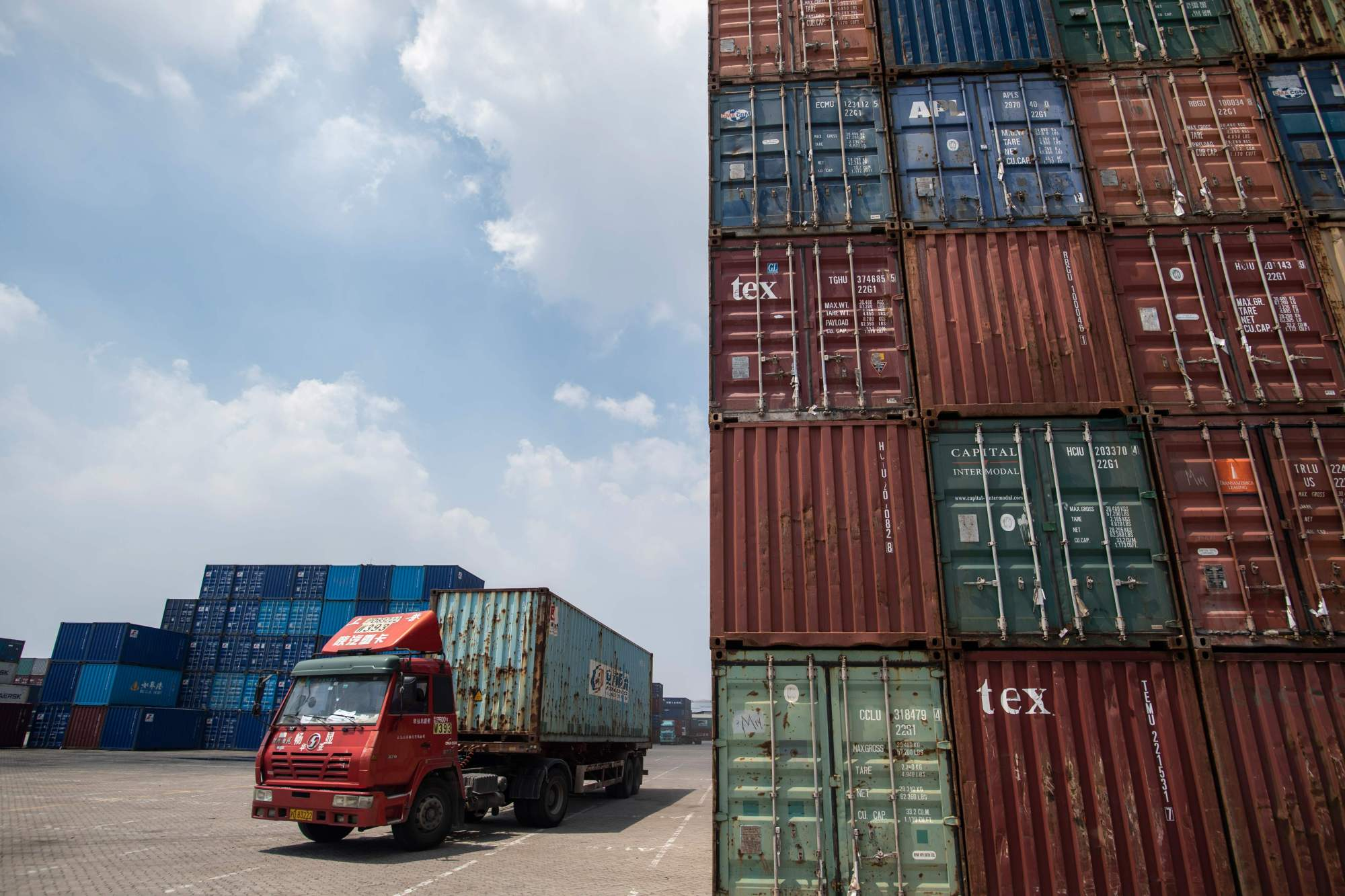 A truck transports containers last month at a port in Zhangjiagang in China's eastern Jiangsu province. | AFP-JIJI