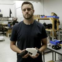 Cody Wilson holds a 3D-printed gun called the Liberator at his shop in Austin, Texas, on Aug. 1. | AP