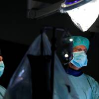 Cardiologist Benjamin Meder performs a heart catheterization at the Heidelberg University Hospital on Aug. 14. | REUTERS