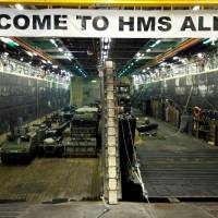 Military vehicles are seen in the loading dock of the HMS Albion, the British Royal Navy flagship amphibious assault ship, after the ship's arrival at Harumi Pier in Tokyo Monday.   REUTERS