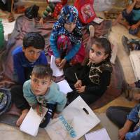 In abandoned villa, war-displaced Syrian kids study on the ground