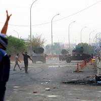 Security forces withdraw from the front of the provincial government building during protests demanding better public services and jobs on Tuesday in Basra, 340 miles southeast of Baghdad. | AP