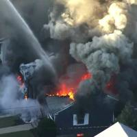 Flames consume the roof of a home in Lawrence, Massachusetts, a suburb of Boston, on Thursday. A series of gas explosions killed a teenager, injured at least 10 other people and ignited fires in at least 39 homes in three communities north of Boston, forcing entire neighborhoods to evacuate as crews scrambled to fight the flames and shut off the gas. | WCVB / VIA AP