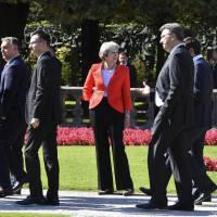British Prime Minister Theresa May watches other heads of government pass after the family photo at the informal EU summit in Salzburg, Austria, on Thursday. | AP