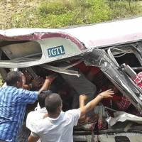 Rescuers reach for passengers from a bus that fell into a gorge in Jagtiyal district of Telangana, India, Tuesday. The bus carrying pilgrims from a Hindu temple in the hills of south India plunged off the road Tuesday, killing more than 50 people, including four children, officials said. | AP