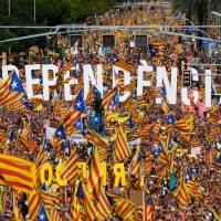 People wave pro-independence Catalan flags 'Esteladas' while holding letters reading 'independence' during a pro-independence demonstration in Barcelona, Spain, Tuesday to mark the National Day of Catalonia, the 'Diada.' Catalan separatists will seek to put on a show of strength and unity at celebrations of the region's national day, nearly a year after a failed attempt to break away from Spain. | AFP-JIJJI