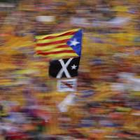 A Catalan pro-independence flag is waved during a demonstration marking the Catalan National Day in Barcelona, Spain, Tuesday. Catalan authorities have made a call to flood the streets of Barcelona later on Tuesday to demand freedom for Catalan politicians in jail and in support of independence from Spain. Sept. 11, called 'Diada,' marks the fall of the Catalan capital to Spanish forces in 1714. | AP
