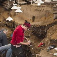 Researchers work inside Blombos Cave on South Africa's southern coast in this photo released Wednesay. | MAGNUS M. HAALAND / HANDOUT / VIA REUTERS