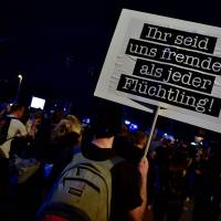 A man holds up a placard that reads 'Ye are more foreign to us than any refugee' after the 'We Are More' concert to say 'No' to the far right on Monday in Chemnitz, eastern Germany, A free concert with several German bands takes place in the town to say 'No' to the far right which has staged nationalist demonstrations after a fatal stabbing allegedly by two foreigners.   JOHN MACDOUGALL / VIA AFP-JIJI