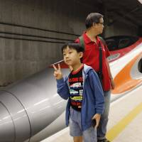 A boy poses beside a Guangzhou-Shenzhen-Hong Kong Express Rail train at the West Kowloon Terminus in Hong Kong on Sunday, the first day of service of the Hong Kong section of the Guangzhou-Shenzhen-Hong Kong Express Rail Link. | AP
