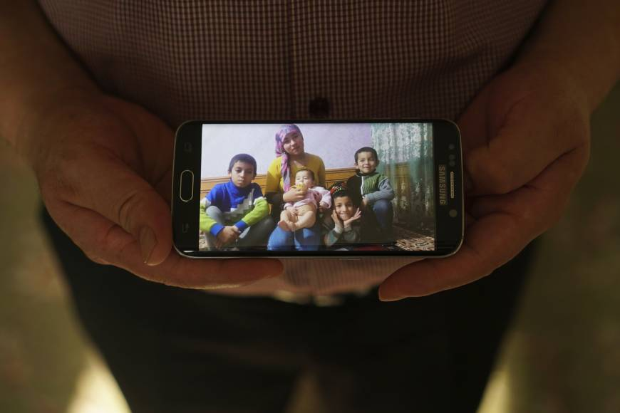 Adil, a businessman from Kashgar, China, with five children, shows an image of his family left behind in China while being interviewed in Istanbul. He got stuck in Turkey during a business trip after hearing that the Chinese government was seizing passports, and hasn't seen his children since. | AP