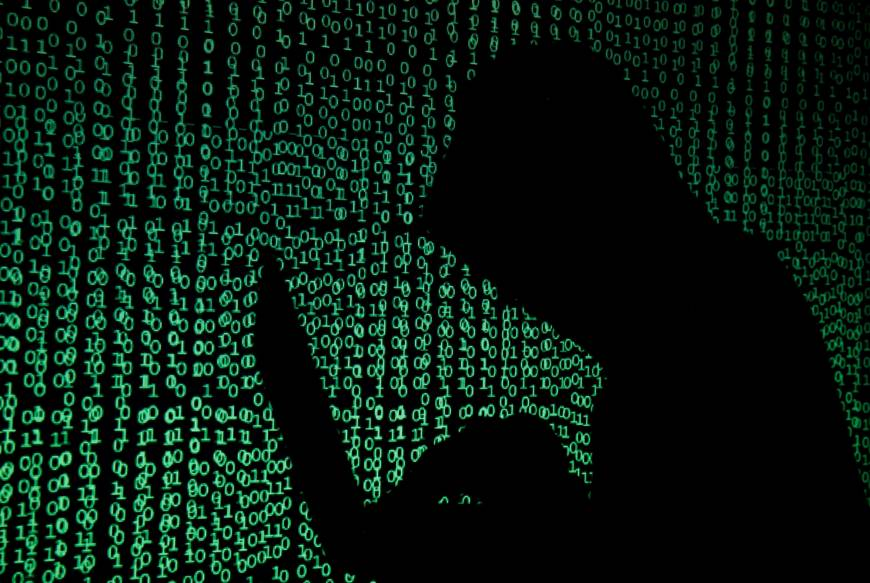 A hooded man holds a laptop computer as cyber code is projected on him in 2017. | REUTERS