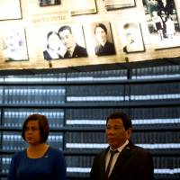 Philippine President Rodrigo Duterte stands beneath pictures of Jews killed in the Holocaust during a visit to the Hall of Names at Yad Vashem's Holocaust History Museum in Jerusalem Monday. | RONEN ZVULUN / VIA REUTERS