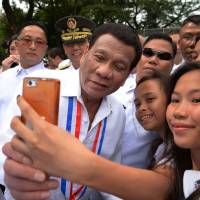 Philippines President Rodrigo Duterte poses for a selfie with students after a wreath-laying ceremony to commemorate National Heroes' Day at the Heroes Cemetery in Manila on Monday. | AFP-JIJI