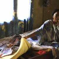 Leoni Kahumbu, mother of Pascaline, a 15-year-old who was infected with Ebola, shows the bed where she first noticed signs of Ebola on her daughter Aug. 26, in Beni, Democratic Republic of Congo. Pascaline was among the first people given mAb114, one of five experimental treatments approved for use in Congo's latest Ebola outbreak. Now she and other survivors must ]deal with the emotional toll of returning to nervous communities where they could be shunned. | AL-HADJI KUDRA MALIRO / VIA AP