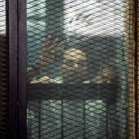 This picture shows detainees inside the soundproof glass dock of the courtroom during the trial of 700 defendants, including Egyptian photojournalist Mahmoud Abu Zeid, widely known as Shawkan, in Cairo on Saturday. An Egyptian court on Saturday handed a five-year jail sentence to prominent photojournalist Zeid, known as Shawkan, who earlier this year received UNESCO's World Freedom Prize. Shawkan was one of more than 700 defendants on trial in the same case, most of them facing charges of killing police and vandalizing property during the clashes. | AFP-JIJI