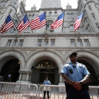 Law enforcement officers stand guard in front of the Trump Hotel in Washington in June. A federal district judge in Washington says a group of nearly 200 Democratic senators and representatives have legal standing to sue U.S. President Donald Trump to prove he violated the U.S. Constitution's emoluments provision. | AP