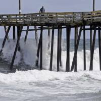 Waves crash under a pier in Kill Devil Hills, North Carolina, Wednesday as Hurricane Florence approaches the East Coast. | AP