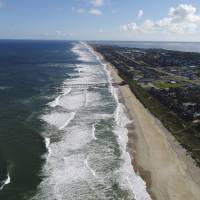 In this Monday afternoon photo provided by DroneBase, waves crash along Avon, North Carolina, in the Outer Banks ahead of Hurricane Florence. Florence churned Tuesday toward the Eastern Seaboard as a storm of 'staggering' size, forcing a million people to evacuate the coast. | DRONEBASE / VIA AP