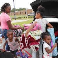 Shatika Young along with her children Jahmari, 3 (left), and Samyah, 2 (right) and niece Christina Young, 11, unpack after arriving at an evacuation shelter at Loris High School as Hurricane Florence approaches the area in Loris, South Carolina, Thursday. | ETHAN HYMAN / THE NEWS