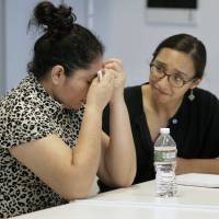 A Guatemalan who was separated from her two children after entering the U.S. in May 2018 and now is among the plaintiffs in a lawsuit against President Donald Trump's administration, seeking monetary damages on behalf of children who were separated from their parents at the border, receives support from a translator after speaking to reporters Thursday in Boston.   AP