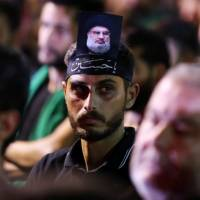 A supporter of Lebanon's Hezbollah leader Sayyed Hassan Nasrallah has his picture on his head, during a live broadcast, the night before Muslim Shiites around the world mark the day of Ashura, in Beirut Wednesday. | REUTERS