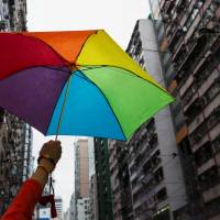 A participant holds a rainbow umbrella as he attends a lesbian, gay, bisexual and transgender Pride Parade in Hong Kong on Nov. 8, 2014. | REUTERS