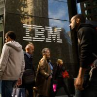 Pedestrians walk past the IBM logo displayed at the company's offices in New York, U.S., in 2013. | BLOOMBERG