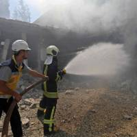 Syrian firefighters try put out a fire in a building that was hit by reported Russian airstrikes in the rebel-hold town of Jadraya, about 35 km southwest of the city of Idlib, on Tuesday. | AFP-JIJI