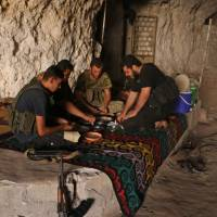 yrian rebel fighters from the recently formed 'National Liberation Front share a meal at an unknown location in the northern countryside of Idlib province on Wednesday. The Russian military confirmed today that airstrikes were carried out on Syria's last major rebel stronghold of Idlib. | AFP-JIJI