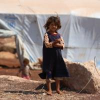 A displaced Syrian girl who fled from regime raids stands outside her tent in a camp in Kafr Lusin near the border with Turkey in the northern part of Syria's rebel-held Idlib province on Sunday. Regime and Russian air raids pounded Syria's last major rebel bastion of Idlib  after an overnight lull, killing at least one child, a monitor said. | AFP-JIJI