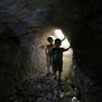 Children walk in a makeshift shelter in an underground cave in Idlib, Syria, Sept. 3.   REUTERS
