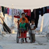 Displaced Syrian children push a disabled boy on a makeshift wheelchair at a camp in Idlib province on Wednesday. | AFP-JIJI