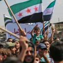 Syrians wave flags during a demonstration in the rebel-held northern city of Idlib on Friday in support of the agreement between Turkey and Russia to avert an assault on Syria's last major rebel stronghold.