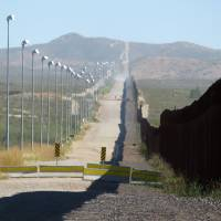 Stadium lights stand along a pedestrian barrier beside the border wall between Douglas, Arizona, and Agua Prieta, in the Mexican state of Sonora, in November 2016.   AP