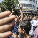 A group of protesters, angry over Iran's economic woes, chant slogans at the main gate of old grand bazaar in Tehran on June 25.