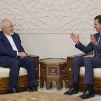 Syrian President Bashar Assad gestures in a meeting with Iran's Foreign Minister Mohammad Javad Zarif in Damascs Monday. | SANA / HANDOUT / VIA REUTERS