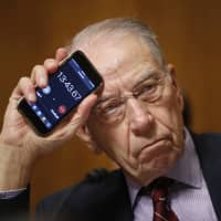 Senate Judiciary Committee Chairman Chuck Grassley holds up a timer on a smartphone to show Sen. Cory Booker how long he has been speaking for during a Senate Judiciary Committee hearing on Supreme Court nominee Judge Brett Kavanaugh on Friday in Washington.   AP