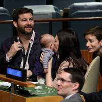 New Zealand Prime Minister Jacinda Ardern kisses her baby, Neve, before speaking at the Nelson Mandela Peace Summit during the 73rd United Nations General Assembly in New York Monday. | REUTERS