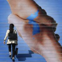 A woman walks on stairs in downtown Seoul on Monday that have been decorated with an image of two hands shaking to form the shape of the Korean Peninsula to support the upcoming inter-Korean summit. | AFP-JIJI