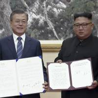 South Korean President Moon Jae-in and North Korean leader Kim Jong Un pose after signing documents in Pyongyang on Wednesday. | AP