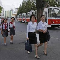 A tram passes North Koreans commuting to work and school in downtown Pyongyang on Thursday.   AP