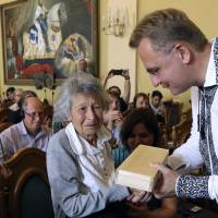 Lviv Mayor Andriy Sadoviy presents a glass copy of an old metal synagogue key to Yanina Hescheles, Polish writer and a Nazi concentration camp survivor, at a ceremony commemorating the 75th anniversary of the annihilation of the city's Jewish population by Nazi Germany in Lviv, Ukraine, Sunday. | YEVHENIY KRAVS / VIA AP