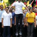 Opposition presidential candidate Ibrahim Mohamed Solih jumps as he walks in a street march with supporters in Male, Maldives, on Saturday
