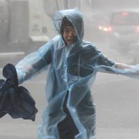 A woman runs in the rain as Typhoon Mangkhut approaches, in Shenzhen, China, on Sunday. | REUTERS